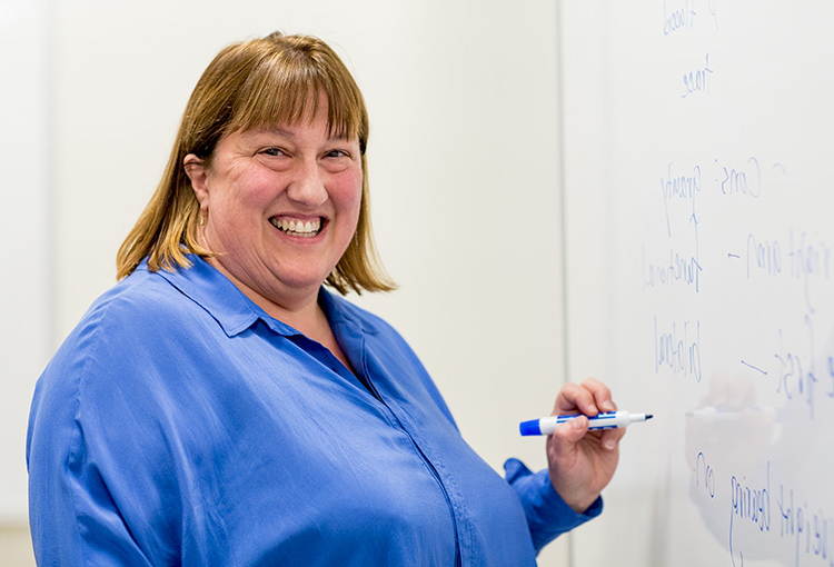 A faculty member standing at a whiteboard holding a marker and smiling at the camera.